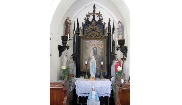 Blick auf den Altar mit Heiligenfigur, Kerzen