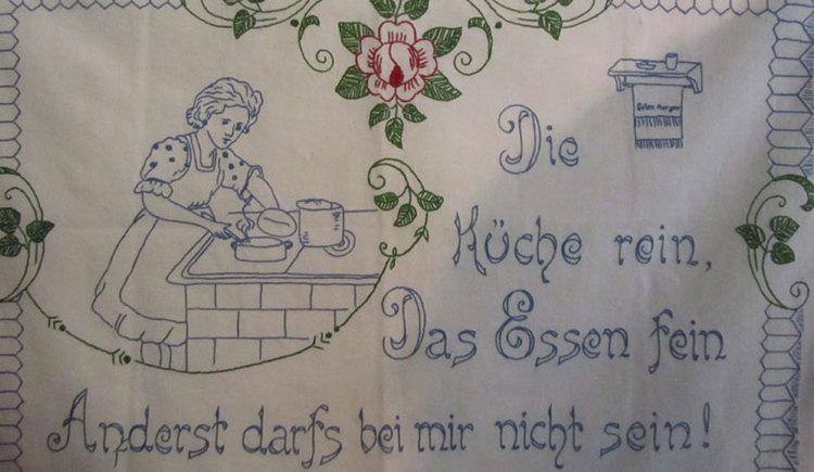 """Stickerei mit der Aufschrift \""""Die Küche rein, das Essen fein. Anderst darfs bei mir nicht sein\"""""""