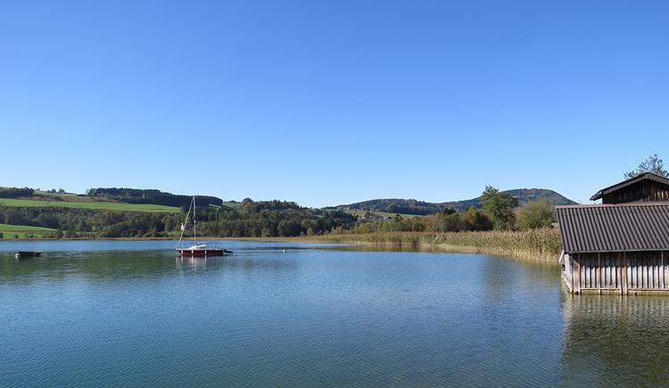 Blick auf das nördliche Ende des Irrsees im Herbst, rechts eine hölzerne Bootshütte, in der Bildmitte ein rotes Segelboot, links daneben ein Ruderboot, beide an einer Boje befestigt. Im Hintergrund Schilfgürtel und dahinter erhebt sich der Irrsberg.