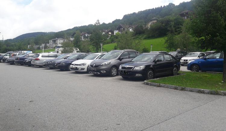 Blick auf den Parkplatz, parkende Autos, im Hintergrund Bäume und Wiesen