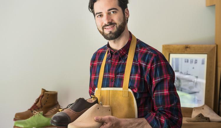 Der Schuster der Goiserer Schuhe steht in seiner Werkstätte und hält einen Goiserer Schuh und ein Schuhleiste in seinen Händen. (© Marc Schwarz - marcschwarz.at)