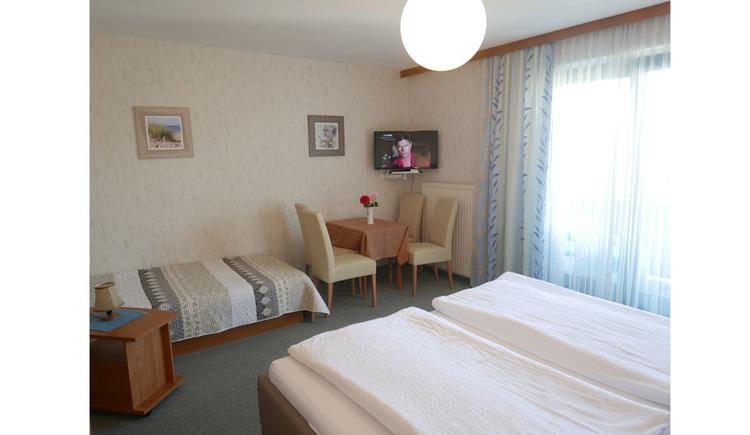 Schlafzimmer mit Doppelbett, seitlich eine Balkontür, im Hintergrund ein Einzelbett, Tisch und Stühle, Fernseher an der Wand