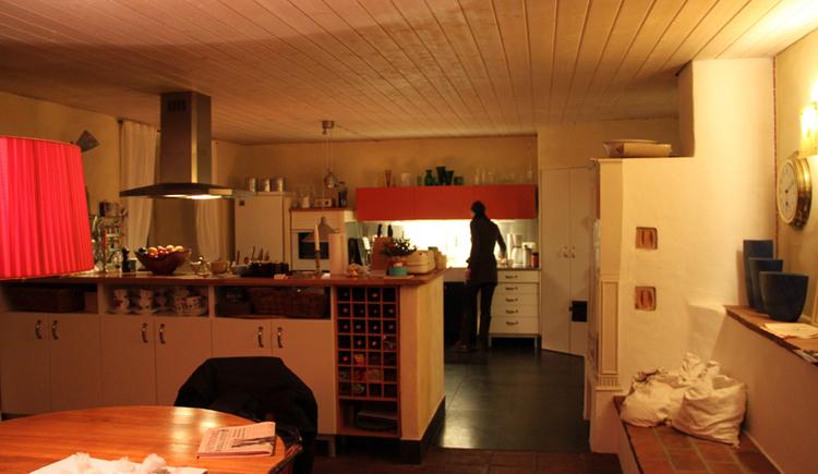im Vordergrund Tisch mit Stuhl, dahinter die voll ausgestattete Küche, seitlich eine Bank