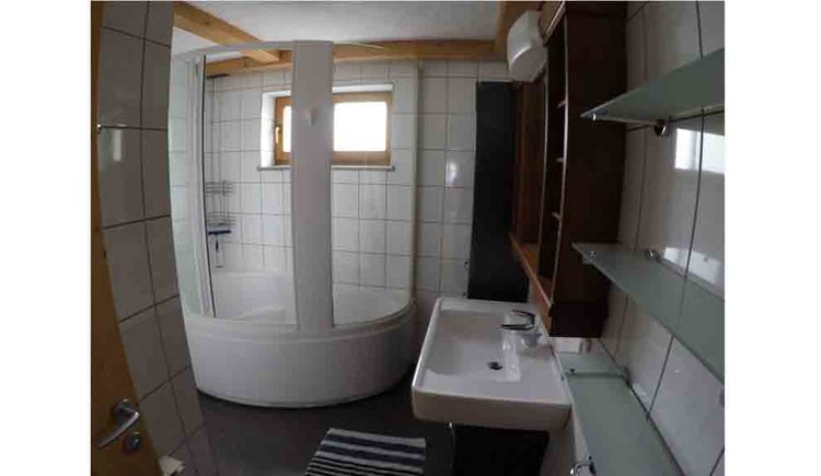 bathroom with shower, washbasin, storage shelve, in the background a window\n