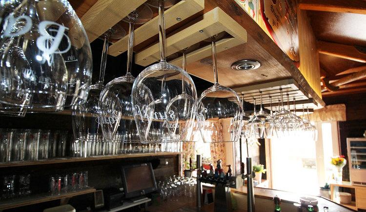 Blick in eine Bar, mit vielen verschiedenen Gläsern. (© Gasthof Fohlenhof)