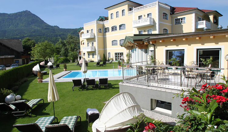 lounger, sunshade, flowers, swimming pool, in the background the hotel and the mountains. (© Sperr-Lehrl)