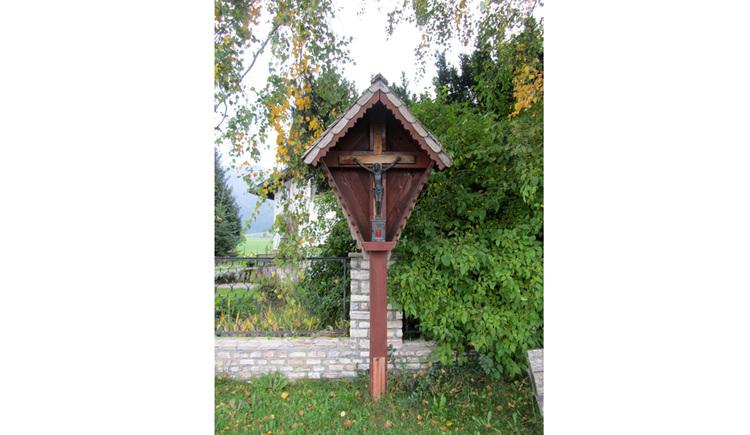 Blick auf das Holzkreuz, davor eine Wiese, dahinter eine Mauer, Sträucher