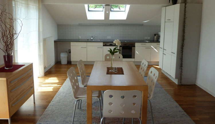 table and chairs, chest of drawer and balcony door on the left side, kitchen with dishwasher, sink, cooker, kettle and coffee machine in the background, skylight\n