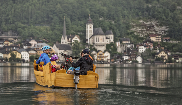 Mountainbikers take a trip in the traditional boats called \