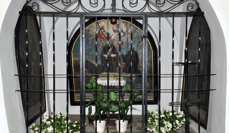Blick durch ein Sperrgitter auf ein Heiligenbild. Blumen