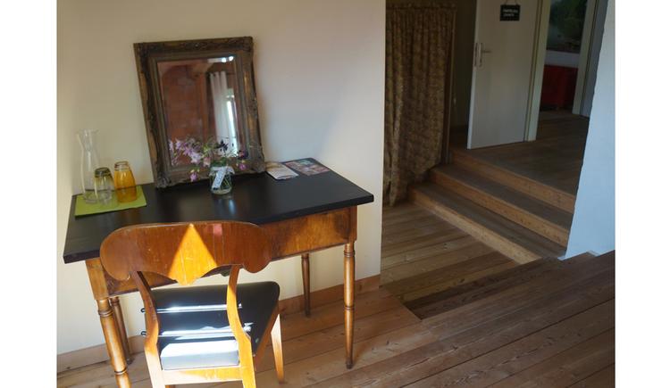 Tisch mit Karaffe und Gläser, Spiegel, Blumen, im Vordergrund ein Sessel