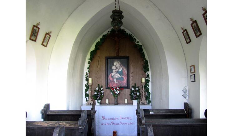 Blick auf den Altar mit Blumen, Kerzen, Heiligenbild, seitlich Holzbänke