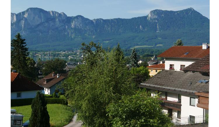 Aussicht vom Balkon auf die Bäume, Wiesen, Häuser, im Hintergrund der See und die Berge