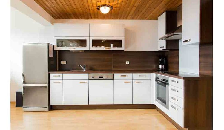 kitchen with fridge, kitchen sink, dishwasher, coffee machine, cooker\n