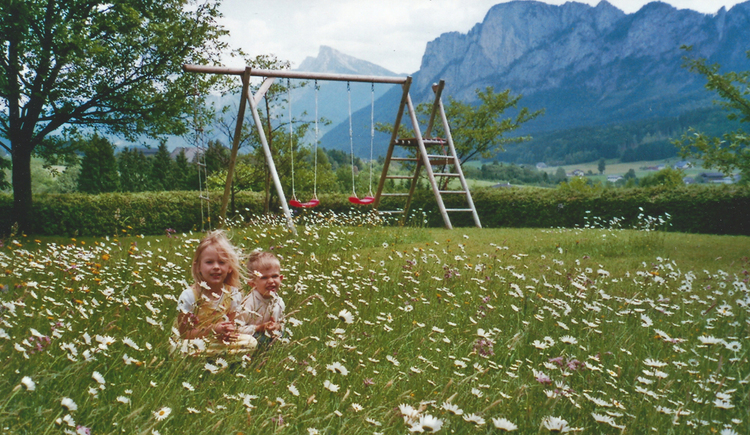 Children are sitting in the blooming meadow, in the background a swing and the mountains