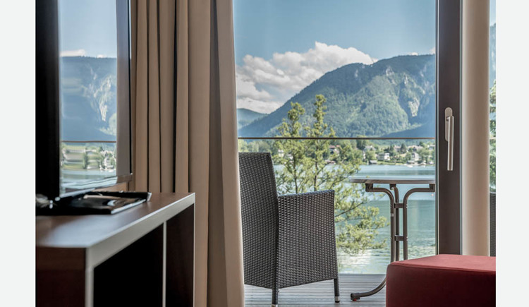 View through the balcony door to the terrace with chair and table, view of the lake and the mountains