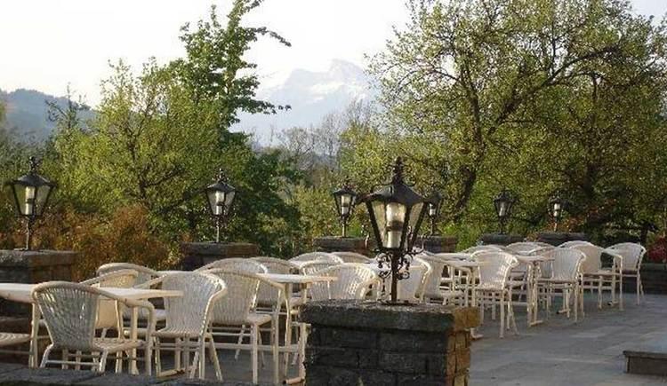 die Terrasse im Morgenlicht, mit Tischen und Stühlen