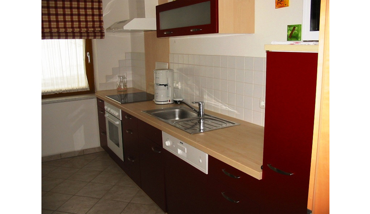 Kitchen with stove, coffee machine, stove, sink, dishwasher, side window