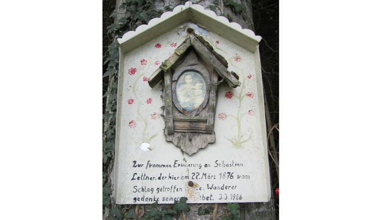 Blick auf eine Holzmarterl auf einem Baum, Heiligenbild, Text