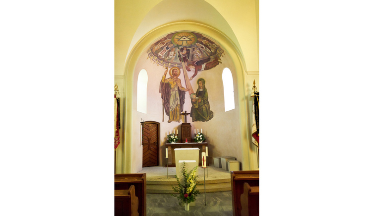 Blick auf den Altar mit Kreuz, Blumen, Gemälde auf der Wand, seitlich Holzbänke