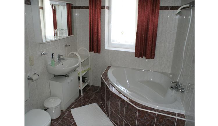 Badezimmer mit Eckbadewanne, seitlich ein Waschbecken, Spiegelschrank, Mülleimer, im Hintergrund ein Fenster