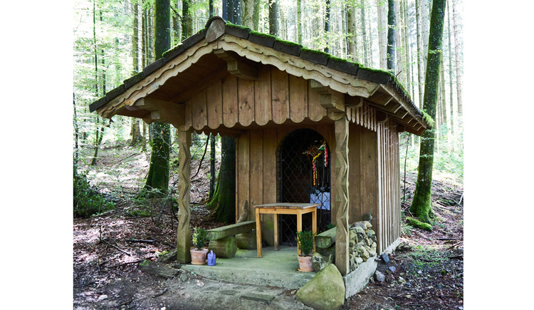 Blick auf eine Holzkapelle im Wald