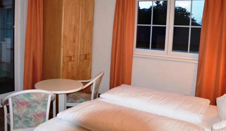 bedroom with double bed, infront of that table and chairs, in the background is a wardrobe and windows\n