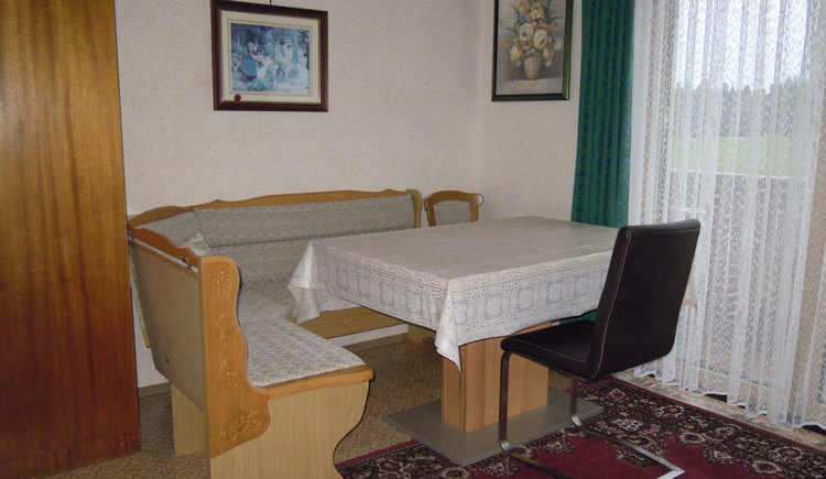 Essbereich mit Eckbank, Tisch und Stuhl, im Hintergrund eine Balkontür