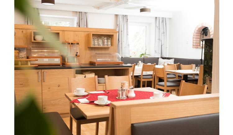 gedeckte Tische, Sessel, im Hintergrund Schränke, Fenster