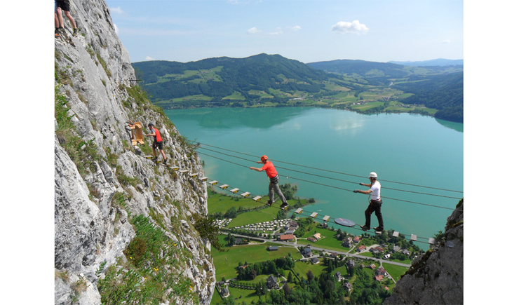 persons are on a suspension bridge, in the background landscape, lake and mountains. (© Tourismusverband MondSeeLand)
