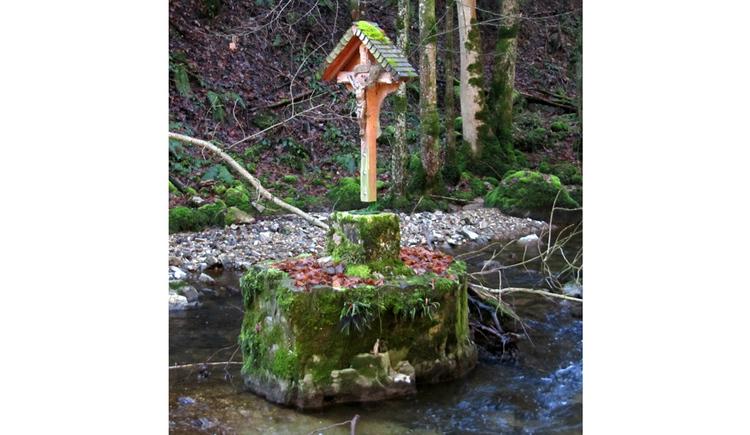 Kreuz steht in einem Bach, im Hintergrund Wald