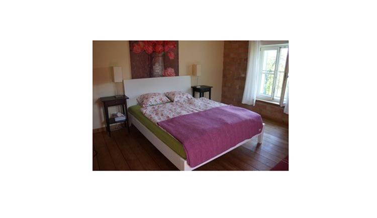 Schlafzimmer mit Doppelbett, dahinter ein Bild, seitlich Nachtkästchen mit Tischlampen, im Hintergrund seitlich ein Fenster