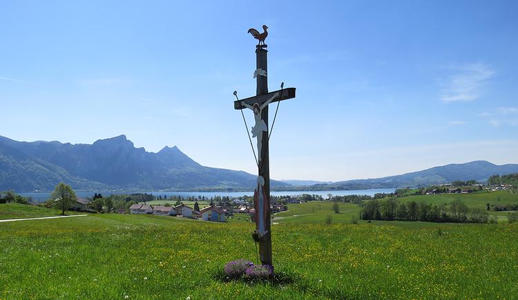 In der Bildmitte das beeindruckende Wetterkreuz von Loibichl mit einem traumhaften Panoramablick über den Mondsee. Im Hintergrund Drachenwand und Schober. (© www.mondsee.at)