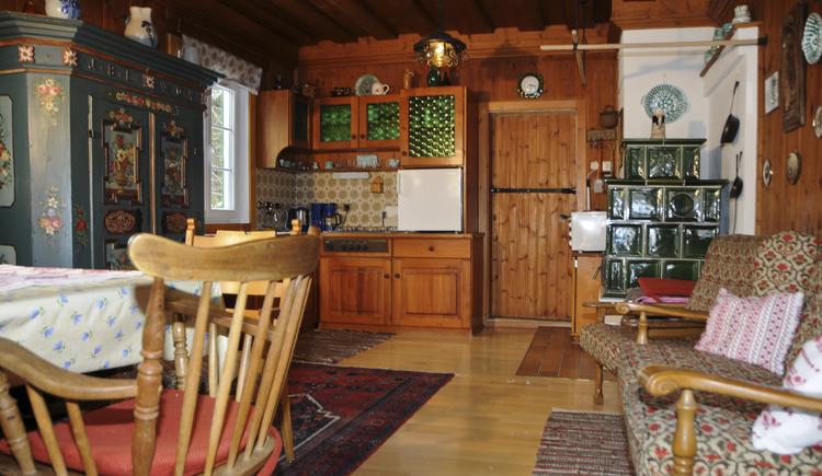 Im urig, mit viel Holz eingerichtete Ferienhaus mit Küchenzeile, Kachelofen und Sitzecke fühlt man sich fast wie auf einer Almhütte