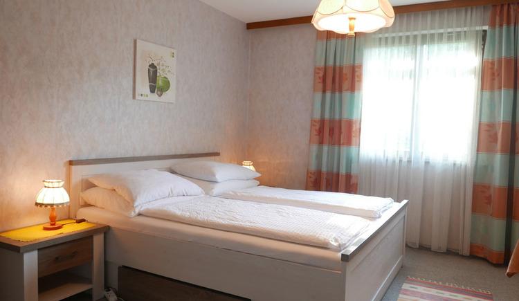 Schlafzimmer mit Doppelbett, Nachtkästchen mit Tischlampen, im Hintergrund ein Fenster