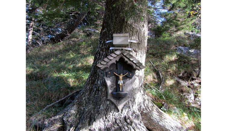 Blick auf ein Holzmarterl an einem Holzstamm