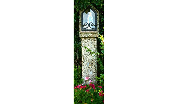 Blick auf den Bildstock mit Marienfigur hinter Glas, Blumen am Boden