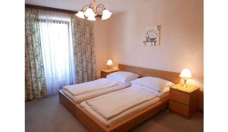 Schlafzimmer mit Doppelbett, Nachtkästchen, Tischlampe, seitlich im Hintergrund eine Balkontür