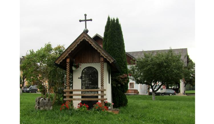 Blick auf die Kapelle mit dem Bauernhaus im Hintergrund