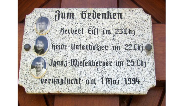 Blick auf eine Gedenktafel mit Fotos und Text