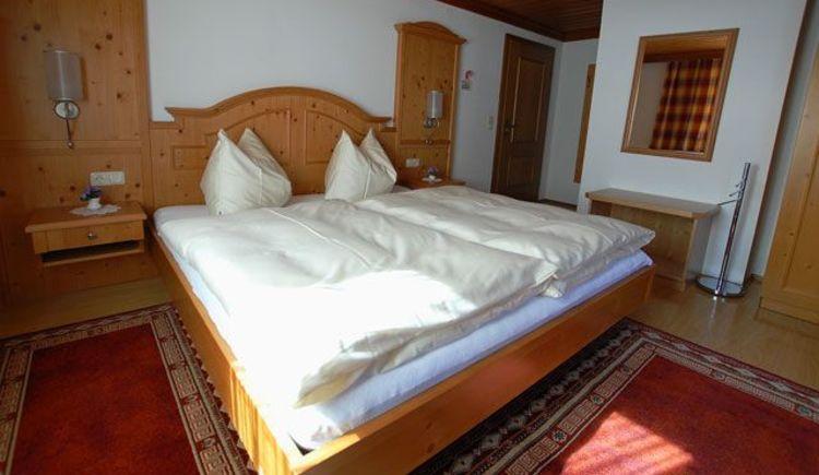 Ein sehr helles Zimmer mit Balkon. Das gemütliche Doppelbett lädt zum Kuscheln ein und der Kleiderschrank bietet genug Stauraum für Ihre Bekleidung. Es befindet sich auch ein kleiner Fernseher im Zimmer. (© Hedwig Gamsjäger)