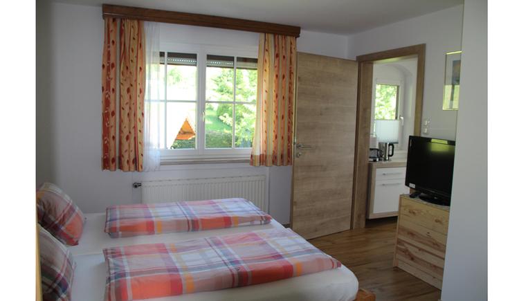 Doppelbett, seitlich ein Fernseher, im Hintergrund ein Fenster
