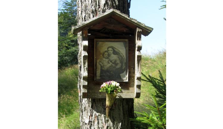 Heiligenbild auf einem Baumstamm, darunter Blumen