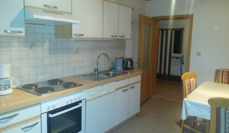 Blick in die Küche, Kaffeemaschine, Herd, Spüle, Wasserkocher, seitlich ein Tisch und Stühle, im Hintergrund eine offene Tür mit Blick in den Vorraum