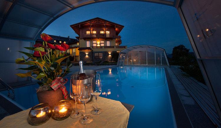 Nacht, Tisch am Pool mit Blumen, Kerzen und Sektkübel, Falsche und Gläser, Blich aufs Haus. (© Leidingerhof)