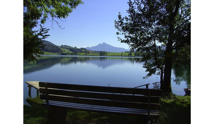 Bench, behind the lake, countryside and mountains