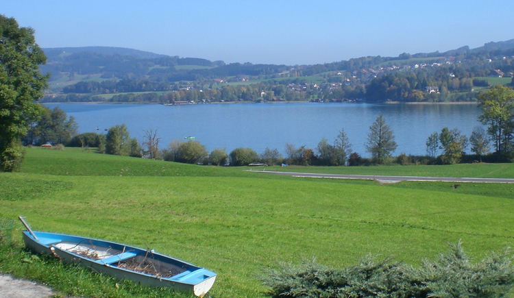 In front of the window n the lawn lies a paddle boat, behind the lake and mountains are visible.