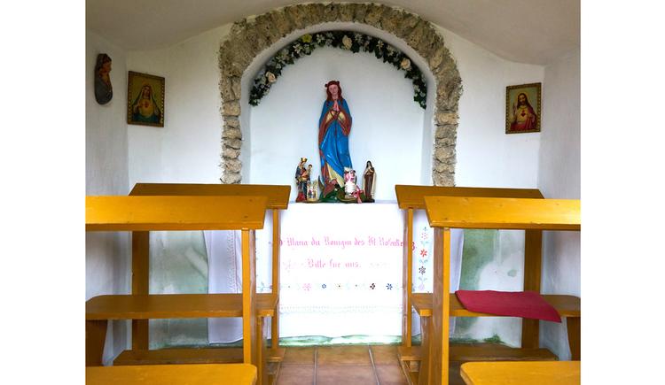 Blick auf den Altar, Heiligenfigur, seitlich Holzbänke