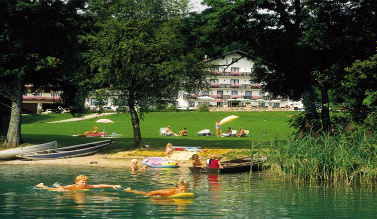 Blick vom See auf das Ufer mit Booten, Personen, Sonnenschirme, Bäume, im Hintergrund das Haus mit Balkon und Blumen