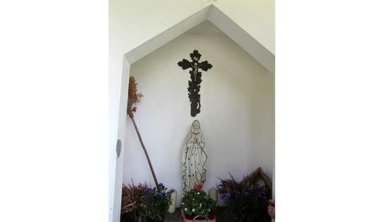 Blick auf eine Heiligenstatue, Kreuz, Blumen
